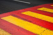 foto of pedestrian crossing  - Pedestrian crossing road marking with yellow and red lines on asphalt - JPG