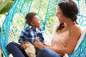 Mother With Baby Son Relaxing On Outdoor Garden Swing Seat