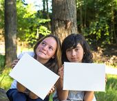 Banner for your message: Two young lovely girl holding clean white sheet paper, in the park.