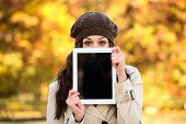 Woman Showing Tablet Screen In Autumn