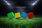 3d colourful cubes in a row against football pitch with bright lights