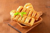 bowl of sausage rolls on wooden cutting board