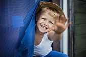 Cheerful kid with straw hat leaning out a window, smiling and waving