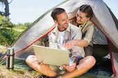 Outdoorsy couple looking at the laptop outside tent on a sunny day