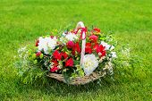 Floral Arrangement With Strawberries In A Basket On The Grass.