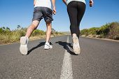 Fit couple running on the open road together on a sunny day