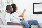 Couple sitting on couch together watching tv at home in the living room