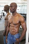 Shirtless muscular man with reflection looking away in gym