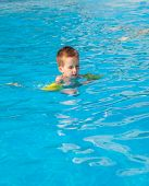picture of floaties  - Happy boy swimming with floaties in swimming pool - JPG