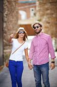Young dates in hats and sunglasses walking outdoors