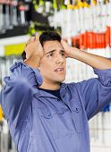 Confused male customer with hands on head looking away in hardware shop