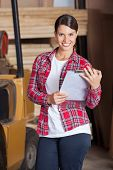 Portrait of confident female supervisor holding clipboard while in workshop