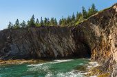 The Rocky Coastline Of Nova Scotia With A Cave