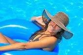 Young woman in bikini wearing a straw hat in the swimming pool