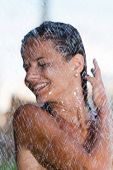 woman in tropical shower in the summertime - Selective focus on the water drops