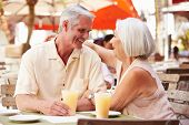 Senior Couple Enjoying Drink In Outdoor Cafe