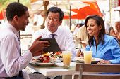 Three Businesspeople Having Meeting In Outdoor Restaurant