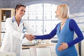 Happy, casual, caucasian, blonde, pregnant woman standing at medical office, shaking hands with doct