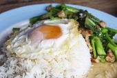 stock photo of crispy rice  - Thai food rice with fried egg on top. Stir fried kale with crispy pork .