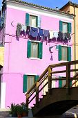Pink Colored House On The Island Of Burano With Clothes Hung Out
