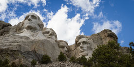 image of mount rushmore national memorial  - view of Mount Rushmore National Monument on a spring morning with some clouds and sunshine - JPG