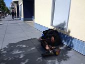 Homeless Person Sleep In Shade Of Tree On Sidewalk To Avoid The Sun With People Walking In The Dista