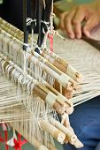 picture of silk worm  - Close up of silk weaved machine with hand - JPG