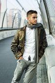 Handsome trendy man standing on a bridge