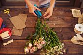 Florist trimming flowers with pruner