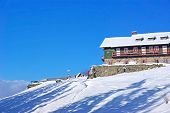 picture of chalet  - Winter mountain chalet and the blue sky behind - JPG