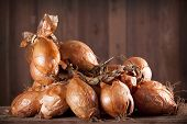 Heap of onions on wooden background