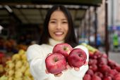 Young Woman Holding Red Apples In Hand At Market Store