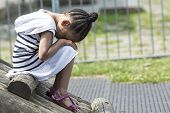 Little young girl sitting in sadness in a playground