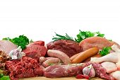 foto of raw chicken sausage  - Fresh butcher cut meat assortment garnished with Salad and fresh rosemary - JPG