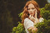 stock photo of grey-haired  - Beautiful red-haired woman with curly long hair and green - grey eyes,freckled,posing for a photograph in the summer the Park on a background of green plants.