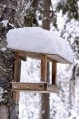 wooden bird table in winter and snow