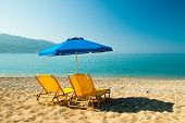 Yellow Sunbeds And Blue Umbrella On A Beautiful Beach In Corfu Island, Greece