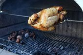 picture of spit-roast  - A spit roasted chicken and roasted chestnuts on the barbeque makes a great  meal - JPG