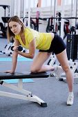 The young girl is engaged in fitness with dumbbells in arms