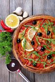 Tasty pizza with spices and round knife on board and wooden table background