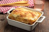 pic of lasagna  - Lasagna bolognese in a baking dish on a rustic table - JPG