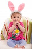 image of baby easter  - Expressive baby girl with fluffy bunny ears eating a Easter toy egg - JPG
