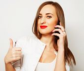 image of long distance relationship  - Pretty young woman using mobile phone over white background - JPG