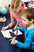 picture of retort  - Girl and boy examines drug for the microscope for learning home table  - JPG