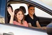 stock photo of say goodbye  - Attractive young couple saying goodbye before driving away in their car - JPG
