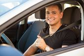 stock photo of seatbelt  - Portrait of a happy Hispanic young man putting his seatbelt on - JPG