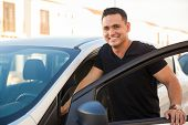 foto of hispanic  - Portrait of a Hispanic young handsome man getting into his car and smiling - JPG