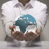 stock photo of environmental protection  - Image of a man in white shirt holding in its hands a glass earth - JPG