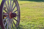 foto of olden days  - Rustic wooden wagon wheel parked on grass - JPG