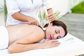 foto of ear candle  - Relaxed brunette getting an ear candling treatment at the spa - JPG